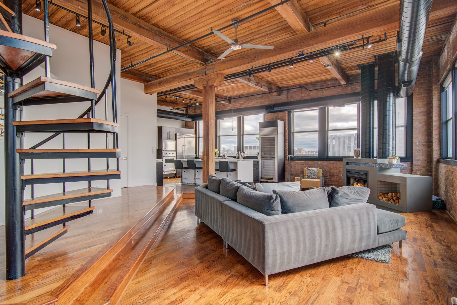 Living Room, Sectional, Chair, Track Lighting, Medium Hardwood Floor, Gas Burning Fireplace, and Ceiling Lighting  Penthouse That Starred on NBC's 'Chicago Fire' Asks $1.775M