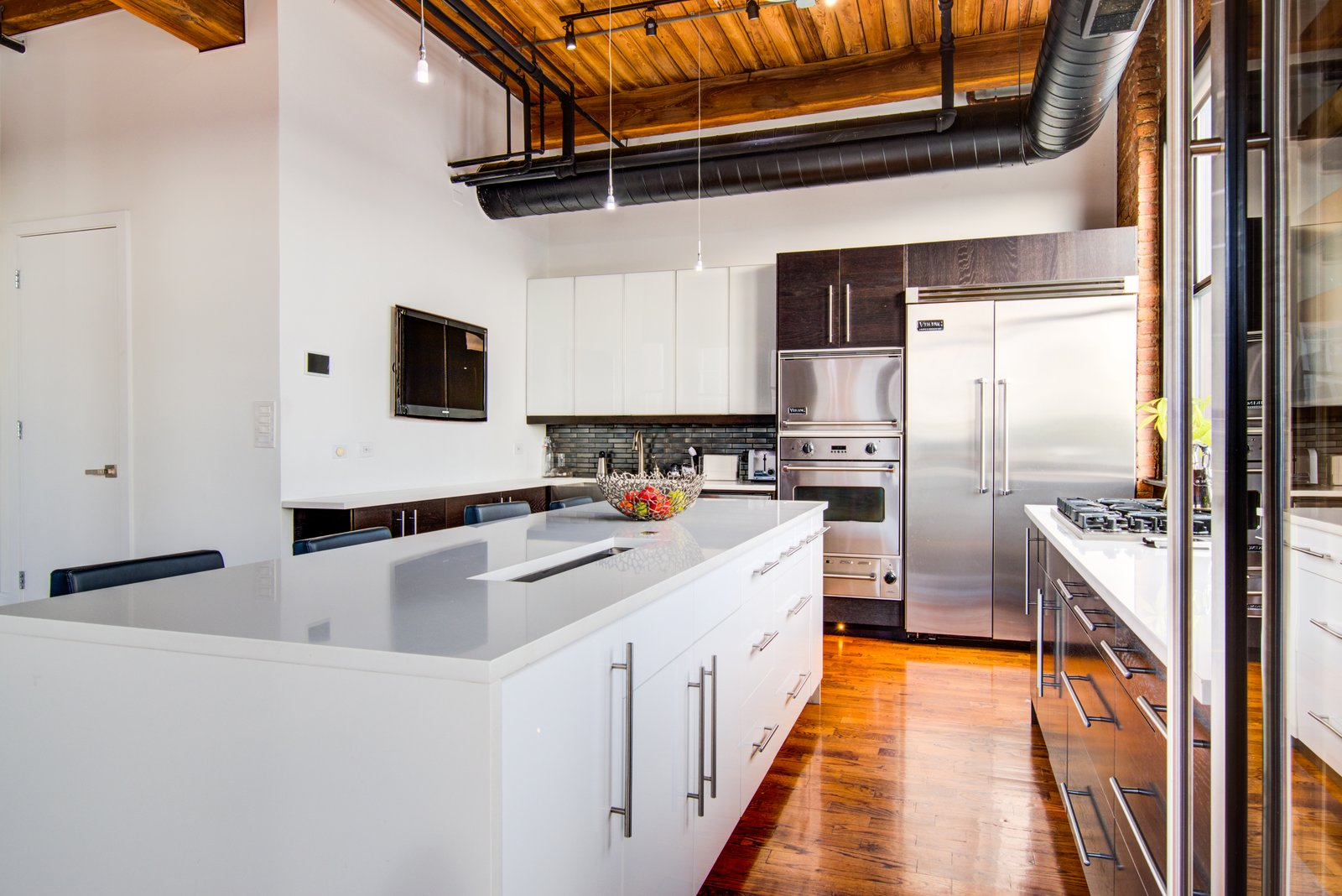 Kitchen, Refrigerator, Cooktops, Medium Hardwood Floor, White Cabinet, Quartzite Counter, Dishwasher, Wall Oven, Ceiling Lighting, Track Lighting, Microwave, and Wine Cooler  Penthouse That Starred on NBC's 'Chicago Fire' Asks $1.775M
