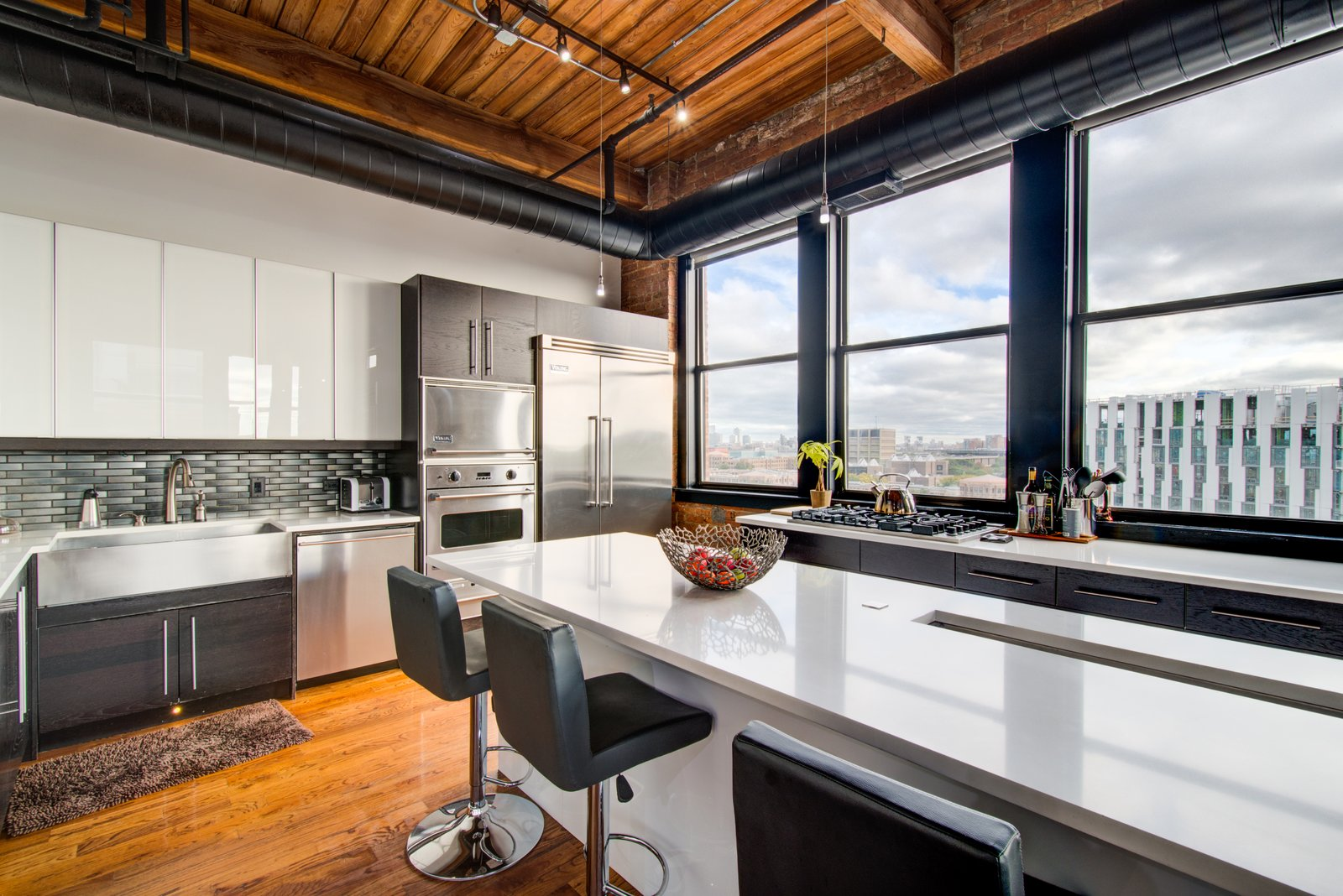 Kitchen, Wine Cooler, Cooktops, Wall Oven, Refrigerator, Medium Hardwood Floor, Microwave, Dishwasher, Quartzite Counter, Ceiling Lighting, Track Lighting, and White Cabinet  Penthouse That Starred on NBC's 'Chicago Fire' Asks $1.775M