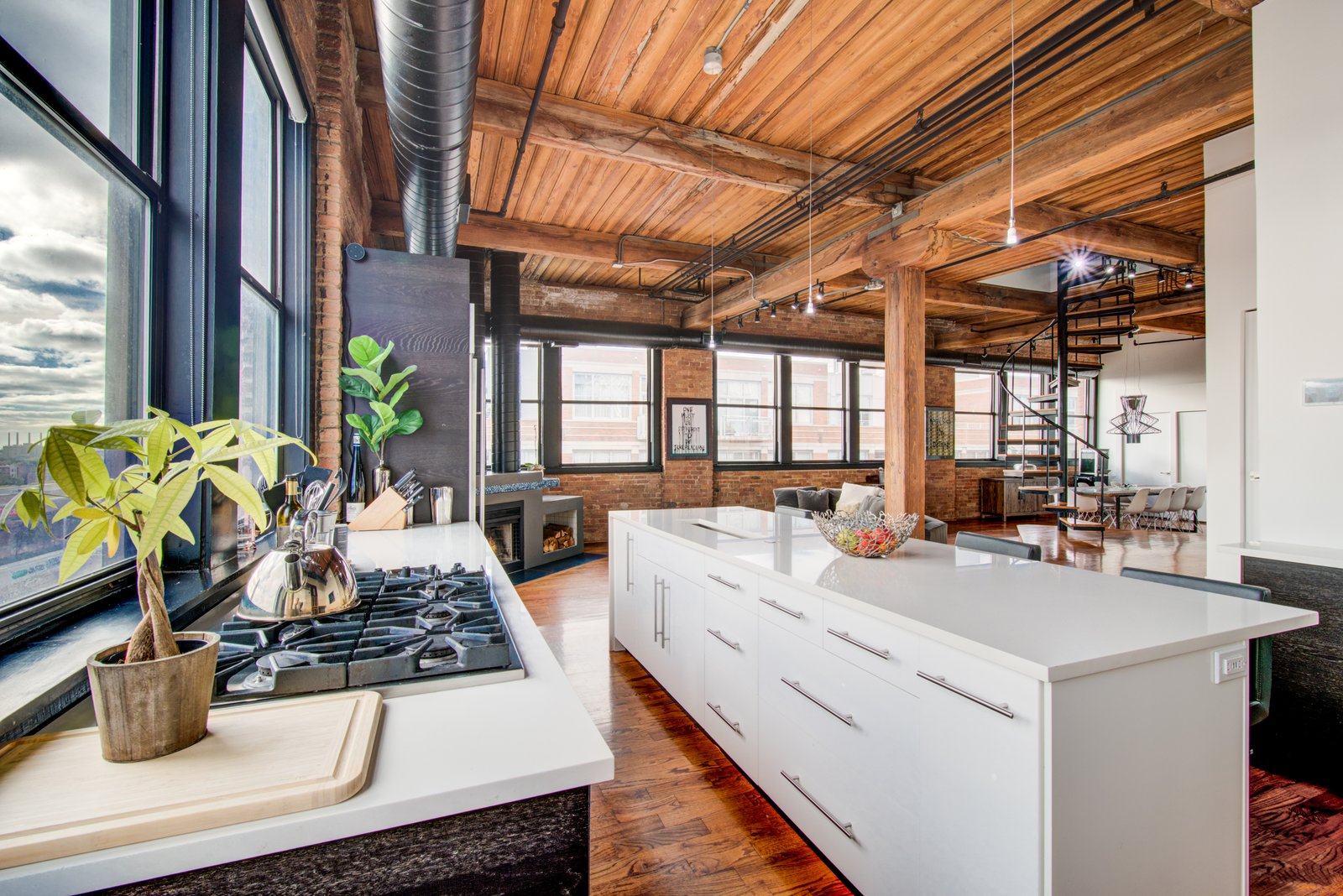 Kitchen, White Cabinet, Cooktops, Medium Hardwood Floor, Track Lighting, Ceiling Lighting, and Quartzite Counter  Penthouse That Starred on NBC's 'Chicago Fire' Asks $1.775M