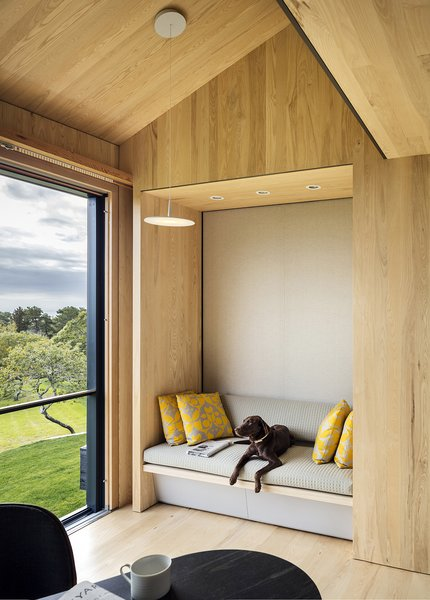 Schiller Projects designed and built many of the Chilmark House's freestanding furniture pieces. In the living area, the family dog reclines on an upholstered bench.