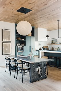 In the kitchen, statement lighting by Nuevo Living, blue-green cabinets, and an intricately carved wooden table juxtaposes modern living with rustic touches.