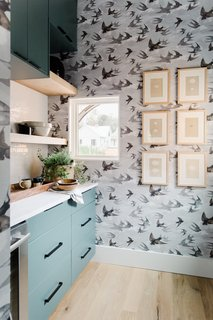 Swallow-printed wallpaper adds depth and pattern to the subdued kitchen color palette.