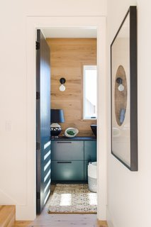 A hidden mudroom near the stairs boasts moody, dark green cabinets, echoing similar colors in the kitchen.
