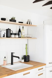 The kitchen area makes use of open shelving and black and white finishes for a crisp look.