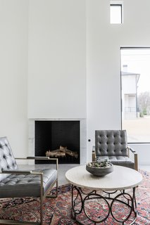 White marble and concrete floors give the fireplace at OKC Modern an industrial edge. The modern home by Butzer Architects and Urbanism is striking yet intimate.