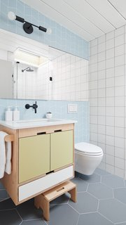 A Fireclay-tiled second bathroom with Kerf cabinets is yet another boon of the extension.
