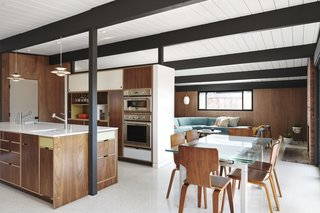 Kitchen, dining, and living spaces seamlessly flow into one another, accentuated by lighting fixtures and furnishings selected by Lin-Tam. In a nod to the vinyl composite tile that comprised the floors of original Eichler houses, commercial solid vinyl tile was chosen for its similar retro, monolithic look.