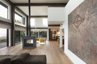 The living area of 2 Barns features a doubled-sided fireplace, hardwood floors, and a neutral color palette. Architect Barry Price prized utilizing local materials in the ADA-accessible home.