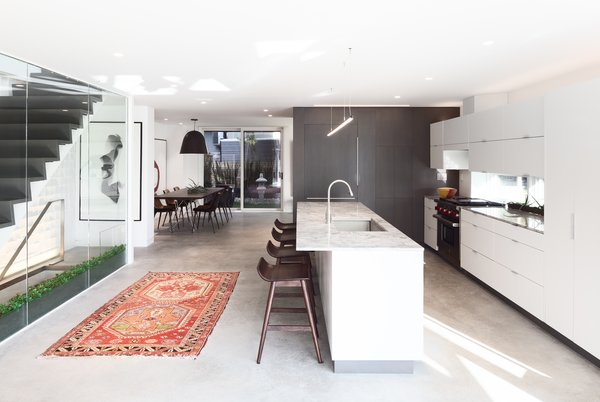 Kitchen, Ceiling Lighting, Refrigerator, Porcelain Tile Backsplashe, White Cabinet, Range, Drop In Sink, Concrete Floor, and Marble Counter  Lakeview in the Beaches by Altius Architecture