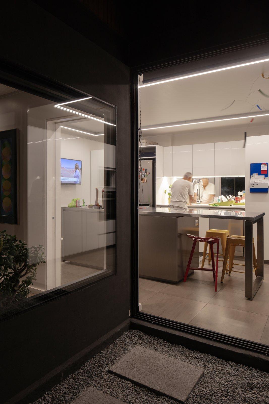Kitchen, Refrigerator, Ceiling Lighting, White Cabinet, Metal Counter, Dishwasher, Ceramic Tile Floor, and Mirror Backsplashe  Virginia House