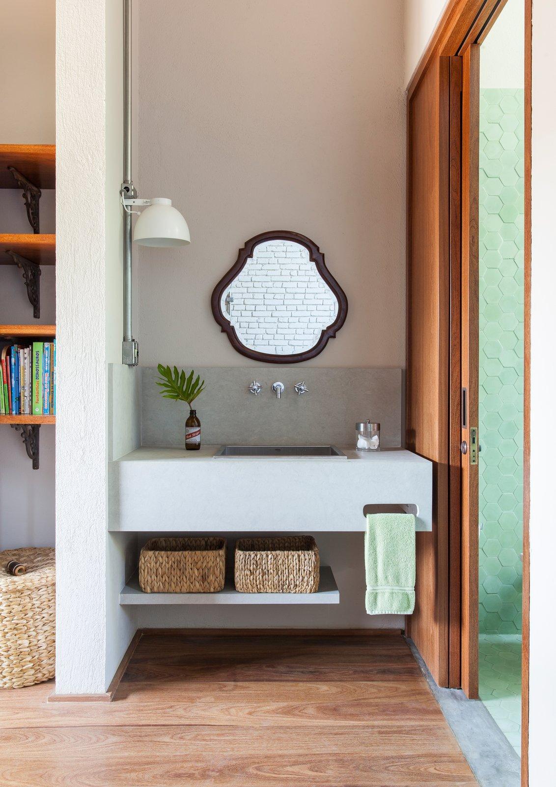 Bath Room, Wall Mount Sink, Concrete Wall, Light Hardwood Floor, and Wall Lighting  Conde D'eu House