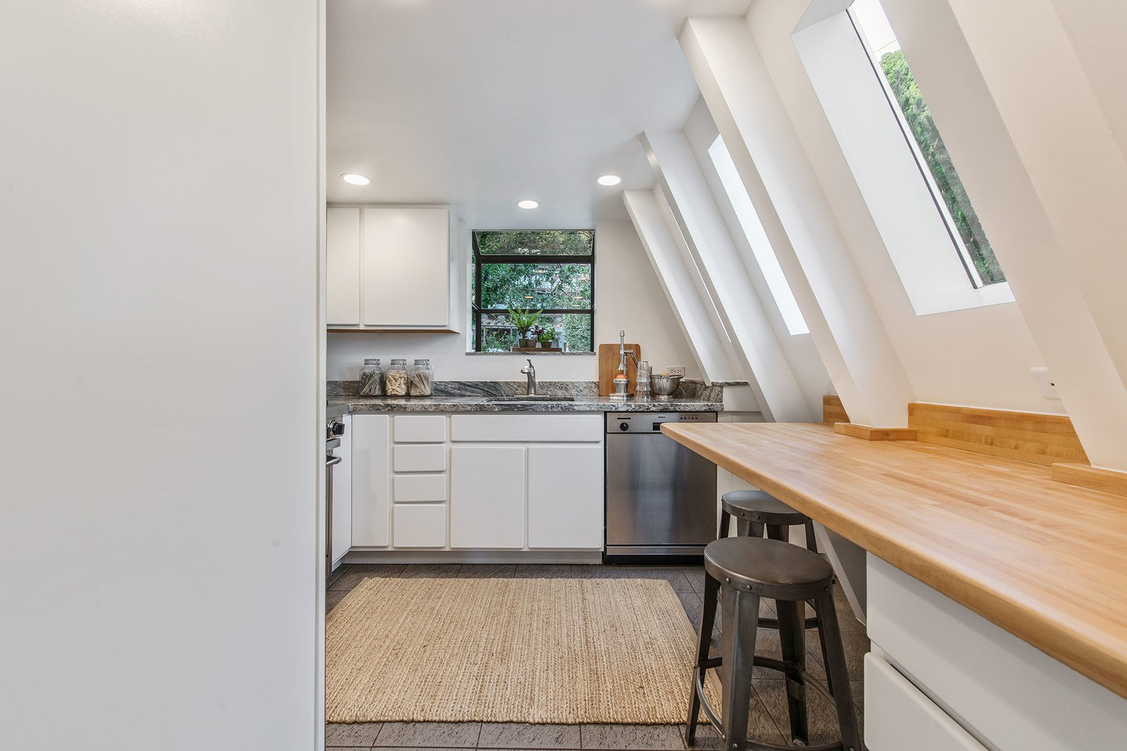Kitchen, White Cabinet, Refrigerator, Dishwasher, Ceiling Lighting, Range, Wall Oven, Recessed Lighting, Drop In Sink, Range Hood, and Stone Counter  Best Photos from Exceptional A-Frame in Sausalito asks $1.399M