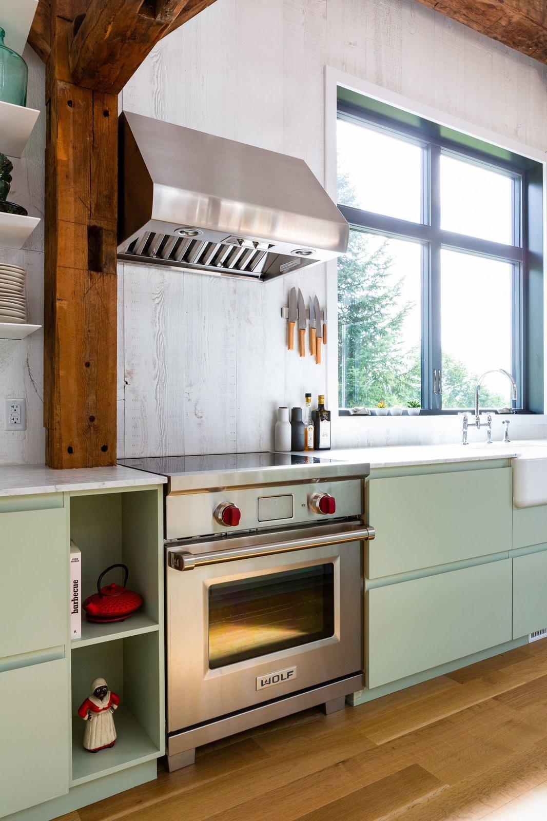 Kitchen, Vessel Sink, Wood Backsplashe, Medium Hardwood Floor, Range, Marble Counter, Range Hood, Colorful Cabinet, and Undermount Sink  The Barn