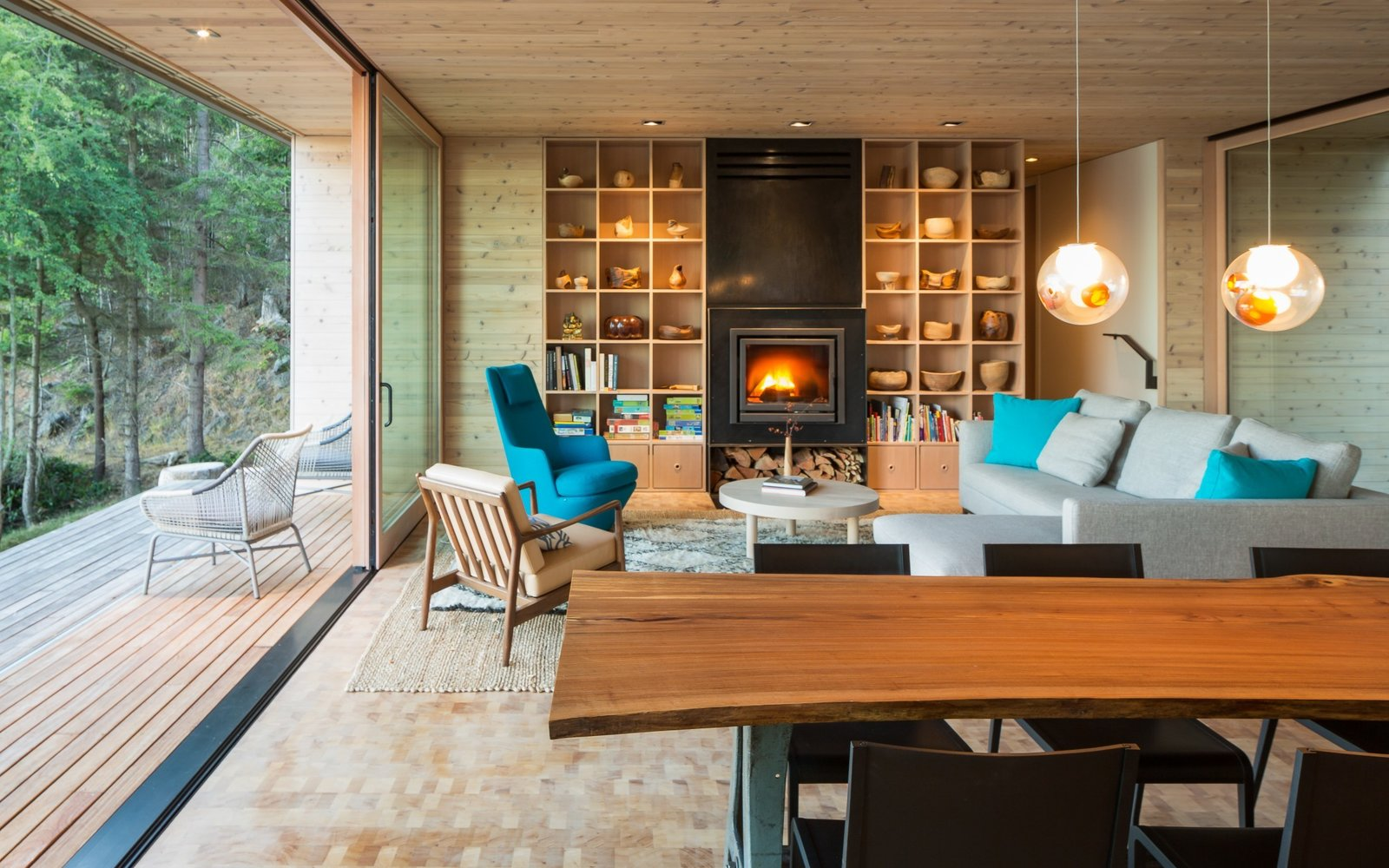 Living Room, Bookcase, Sofa, End Tables, Standard Layout Fireplace, Ceiling Lighting, Sectional, Medium Hardwood Floor, Gas Burning Fireplace, Chair, Coffee Tables, and Bench  Lone Madrone Cabin by Heliotrope Architects