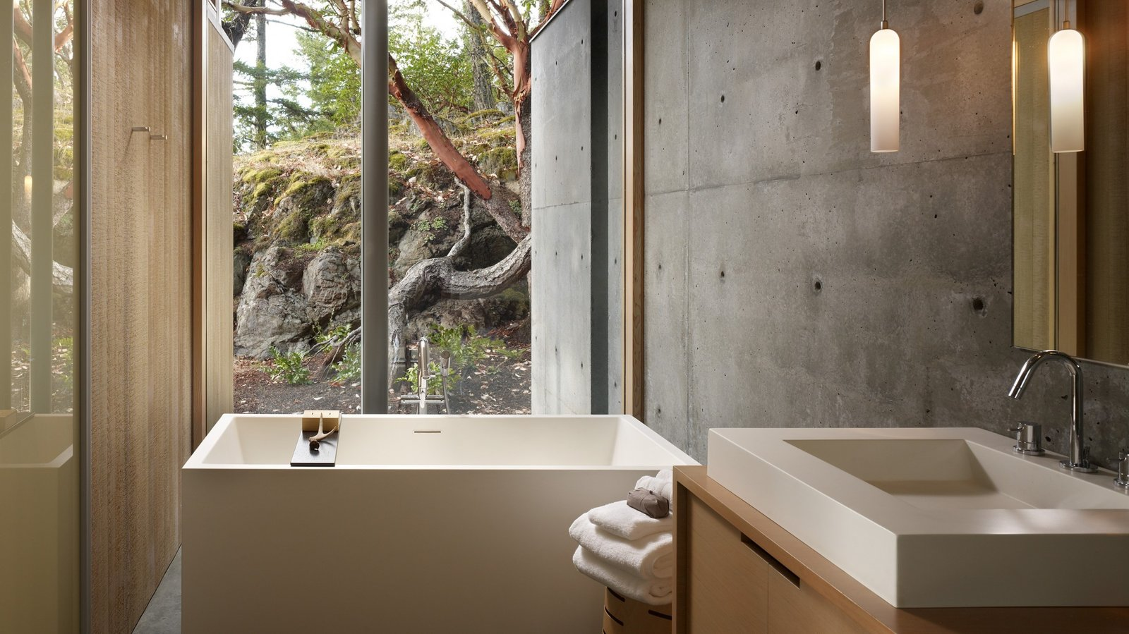Bath Room, Pendant Lighting, Freestanding Tub, Ceiling Lighting, Vessel Sink, Accent Lighting, Concrete Floor, Concrete Wall, Soaking Tub, and Wood Counter  Suncrest Residence by Heliotrope Architects