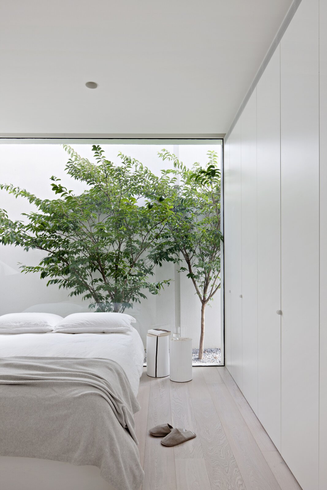 Bedroom, Night Stands, Light Hardwood Floor, Bed, and Ceiling Lighting  Photo 6 of 6 in An Introspective Home in Melbourne Offers Garden Views at Every Turn
