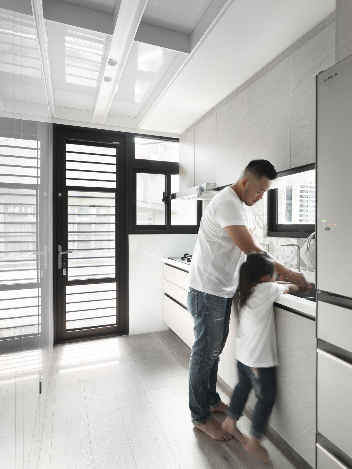 带有厨房,天花板照明,浅色硬木地板,镜子后壁板,水槽,冰箱和彩色橱柜的现代住宅。 日常生活的隐形秩序照片4