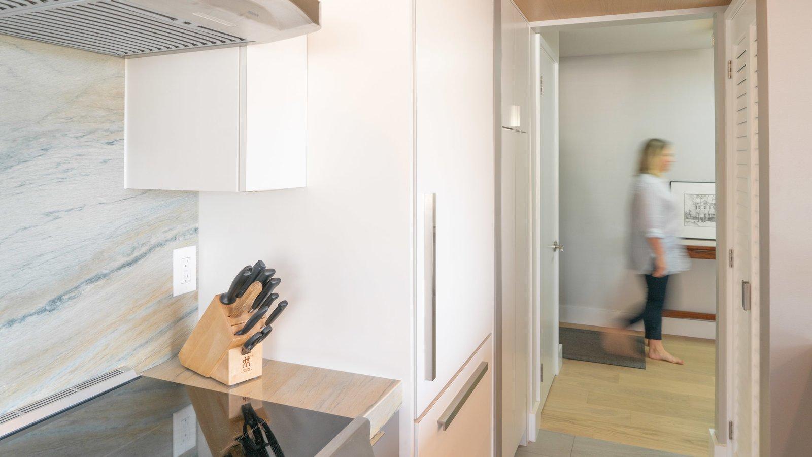 Kitchen, Granite Counter, Ceramic Tile Floor, White Cabinet, Range, Stone Slab Backsplashe, Range Hood, and Refrigerator  Scott Residence by District Architecture + Design
