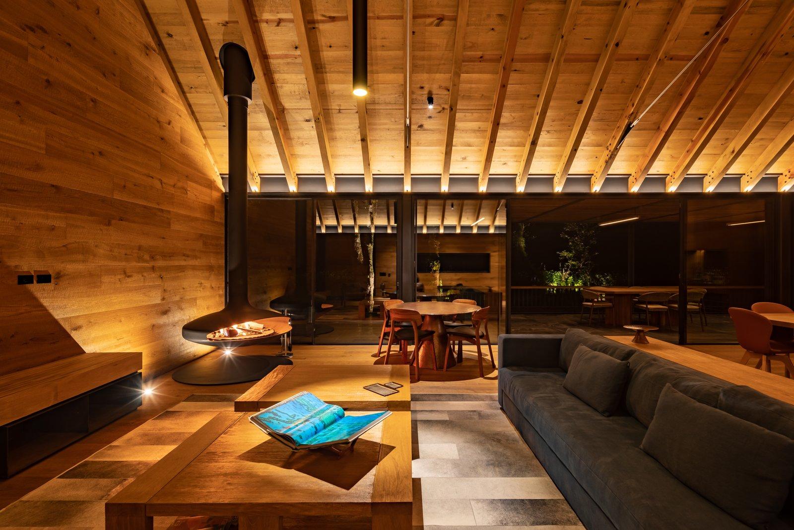 Living Room, Bench, Wall Lighting, Hanging Fireplace, Medium Hardwood Floor, Sofa, and Ceiling Lighting  L7 Home by Augusto Fernandez