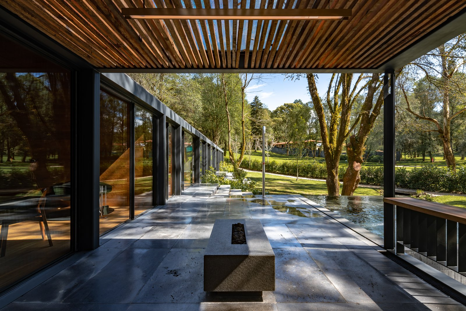 Outdoor, Trees, Stone Patio, Porch, Deck, Back Yard, Hanging Lighting, Grass, Wood Patio, Porch, Deck, Landscape Lighting, Infinity Pools, Tubs, Shower, Large Patio, Porch, Deck, and Small Pools, Tubs, Shower  L7 Home by Augusto Fernandez