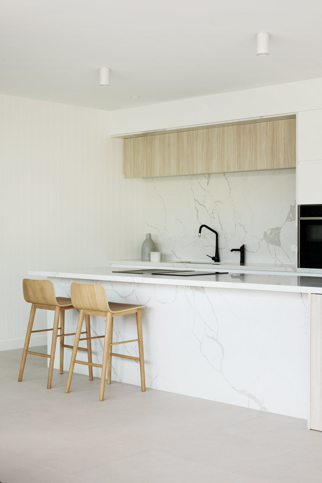 Kitchen, Ceiling Lighting, Stone Counter, Ceramic Tile Floor, Stone Slab Backsplashe, Cooktops, White Cabinet, and Wall Oven  Warraweena