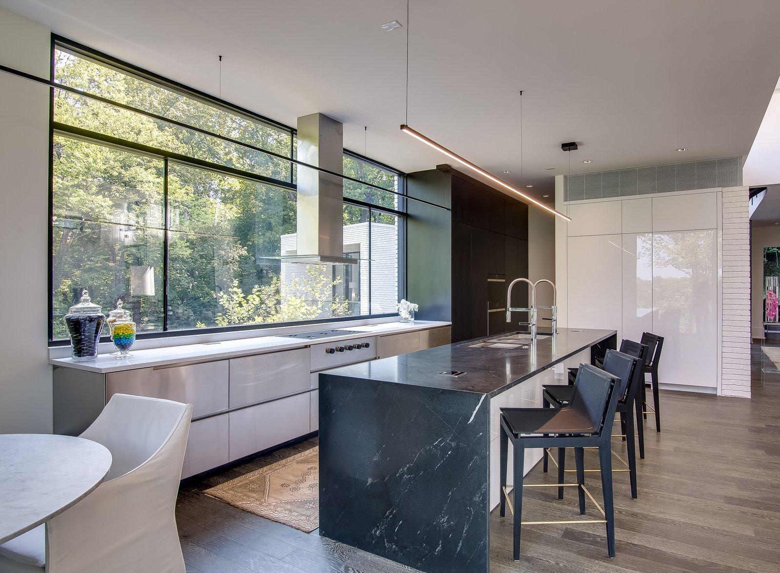 Kitchen, Granite Counter, Refrigerator, Metal Cabinet, Range, Undermount Sink, Cooktops, Dark Hardwood Floor, Range Hood, White Cabinet, Wall Oven, Pendant Lighting, and Marble Counter  Modern View