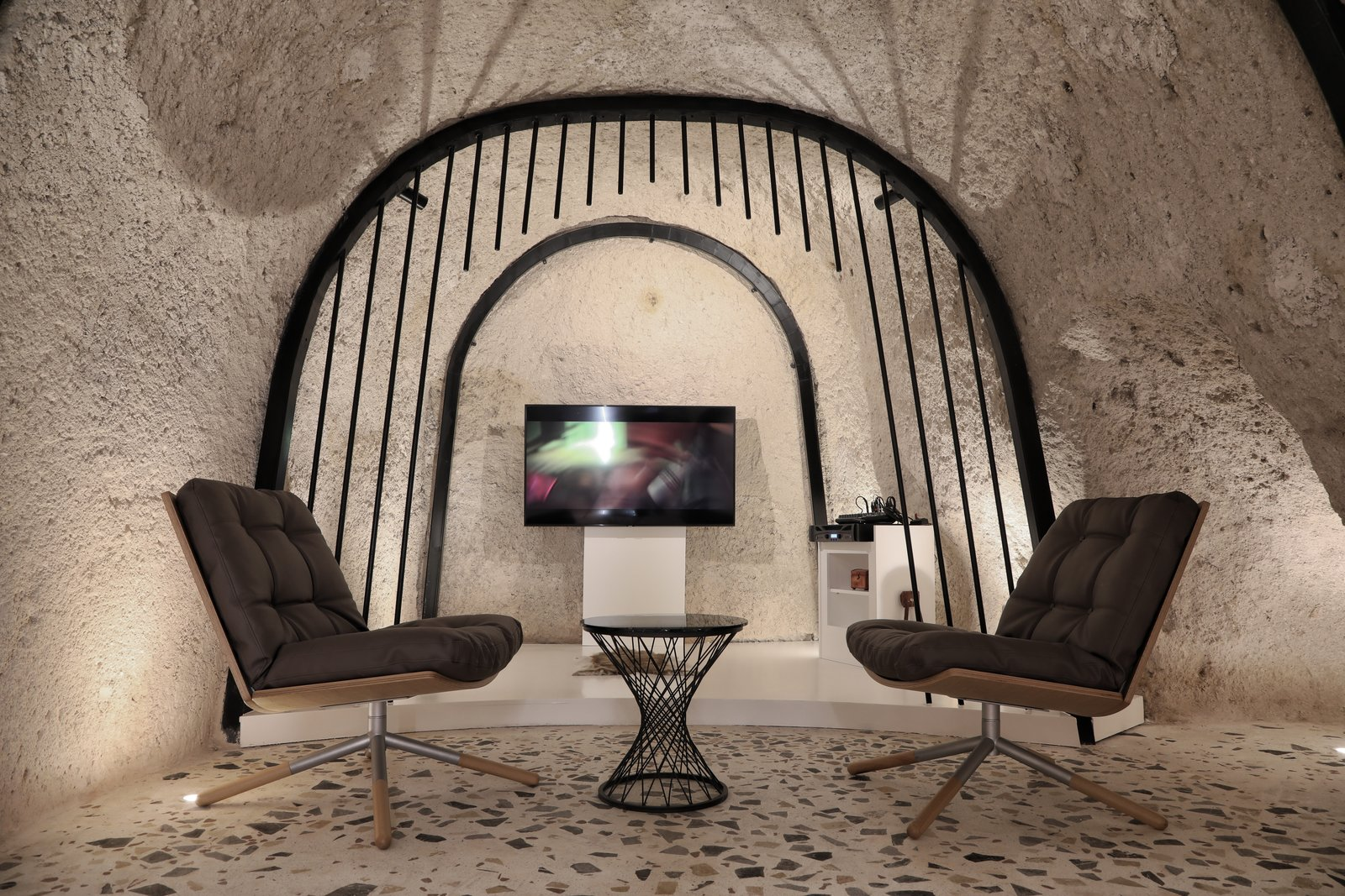 Living Room, Chair, Floor Lighting, End Tables, and Terrazzo Floor  Photo 6 of 13 in A Primal Space Gets a Swanky, Modern Twist in This Turkish Cave Loft