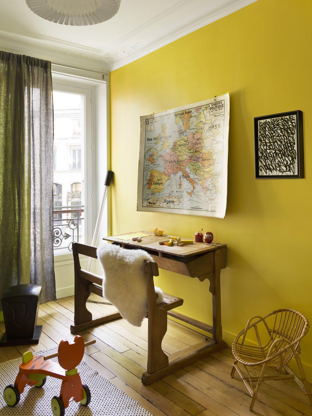 Kids Room, Playroom Room Type, Medium Hardwood Floor, Rug Floor, Chair, Neutral Gender, Toddler Age, and Desk  Photo 10 of 12 in Street Art Meets Vintage Pieces in a Chic Parisian Renovation