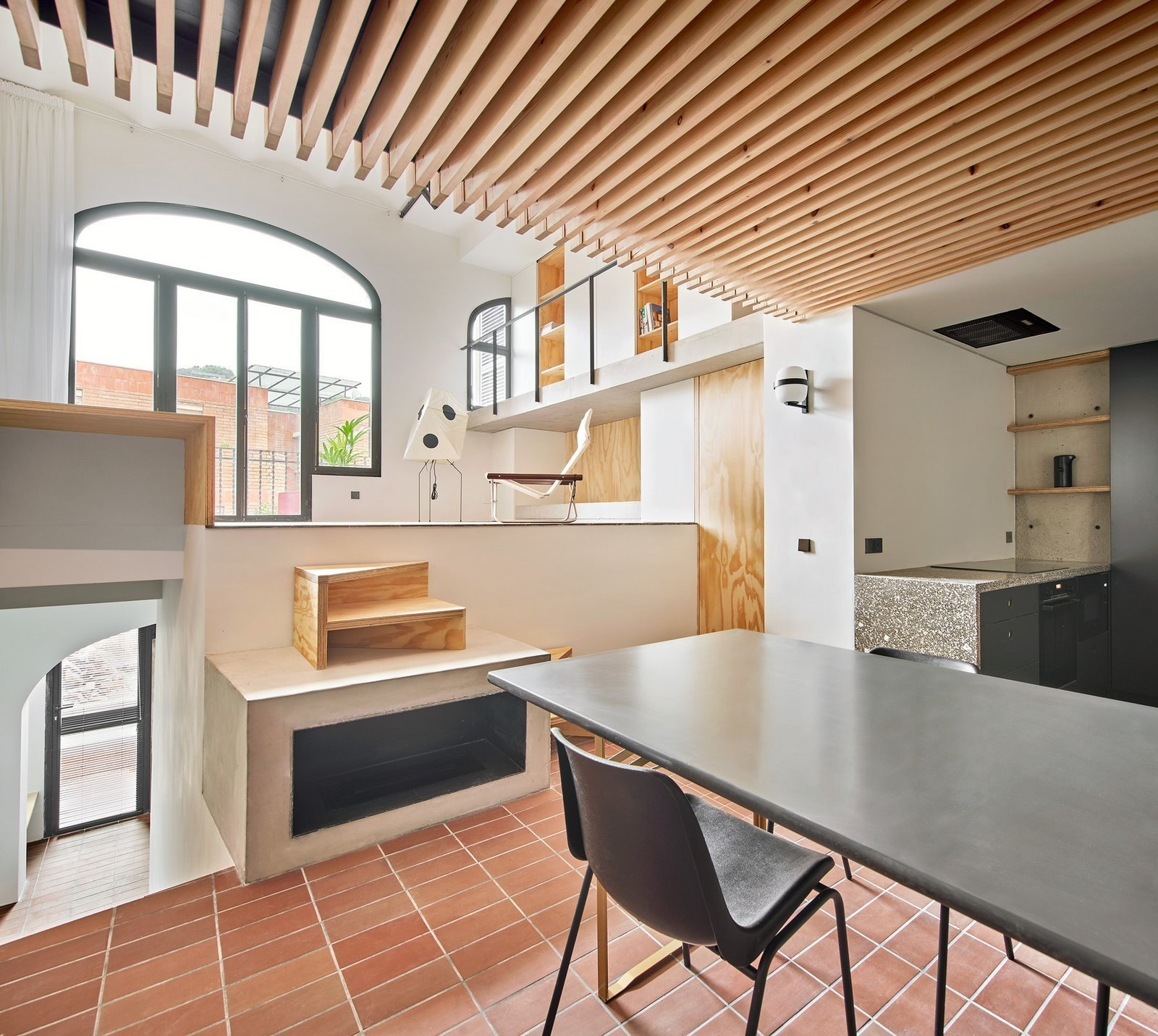 Dining Room, Table, Ceramic Tile Floor, Wood Burning Fireplace, Wall Lighting, and Chair  Photo 9 of 15 in A Renovation Turns a Once-Abandoned Barcelona Building Into an Airy Home