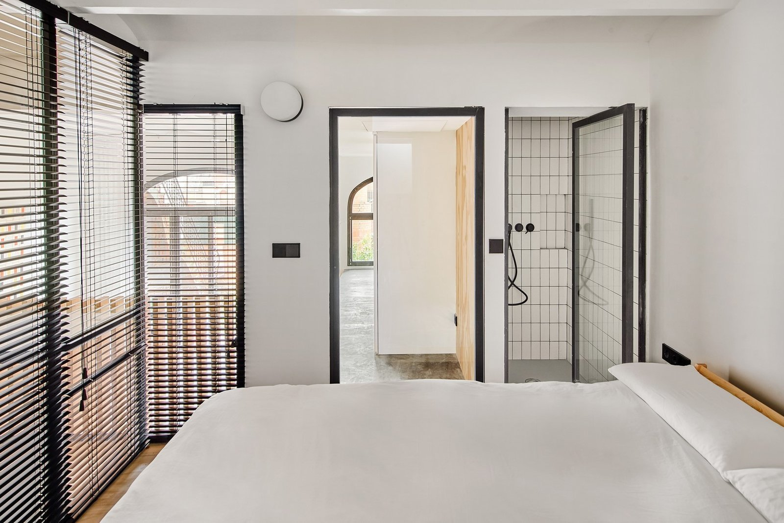 Bedroom, Accent Lighting, Wall Lighting, Bed, and Medium Hardwood Floor  Photo 11 of 15 in A Renovation Turns a Once-Abandoned Barcelona Building Into an Airy Home