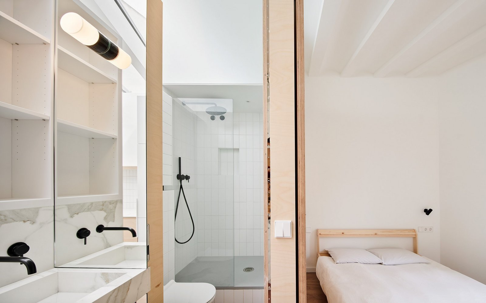Bath Room, Marble Counter, One Piece Toilet, Wall Mount Sink, Open Shower, and Accent Lighting  Photo 9 of 17 in Picture Windows and Sliding Doors Work Magic in This Cozy Barcelona Home from The Akari House