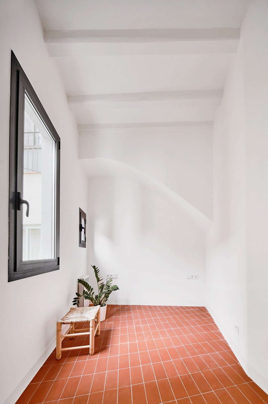 Hallway and Terra-cotta Tile Floor  Photo 15 of 17 in Picture Windows and Sliding Doors Work Magic in This Cozy Barcelona Home from The Akari House