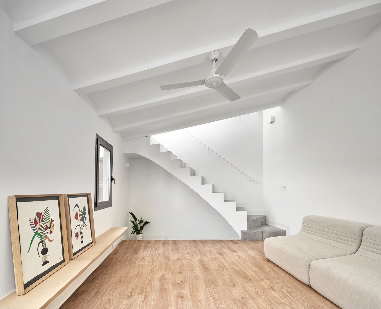 Living Room, Shelves, Ceiling Lighting, Sofa, and Medium Hardwood Floor  Photo 4 of 17 in Picture Windows and Sliding Doors Work Magic in This Cozy Barcelona Home