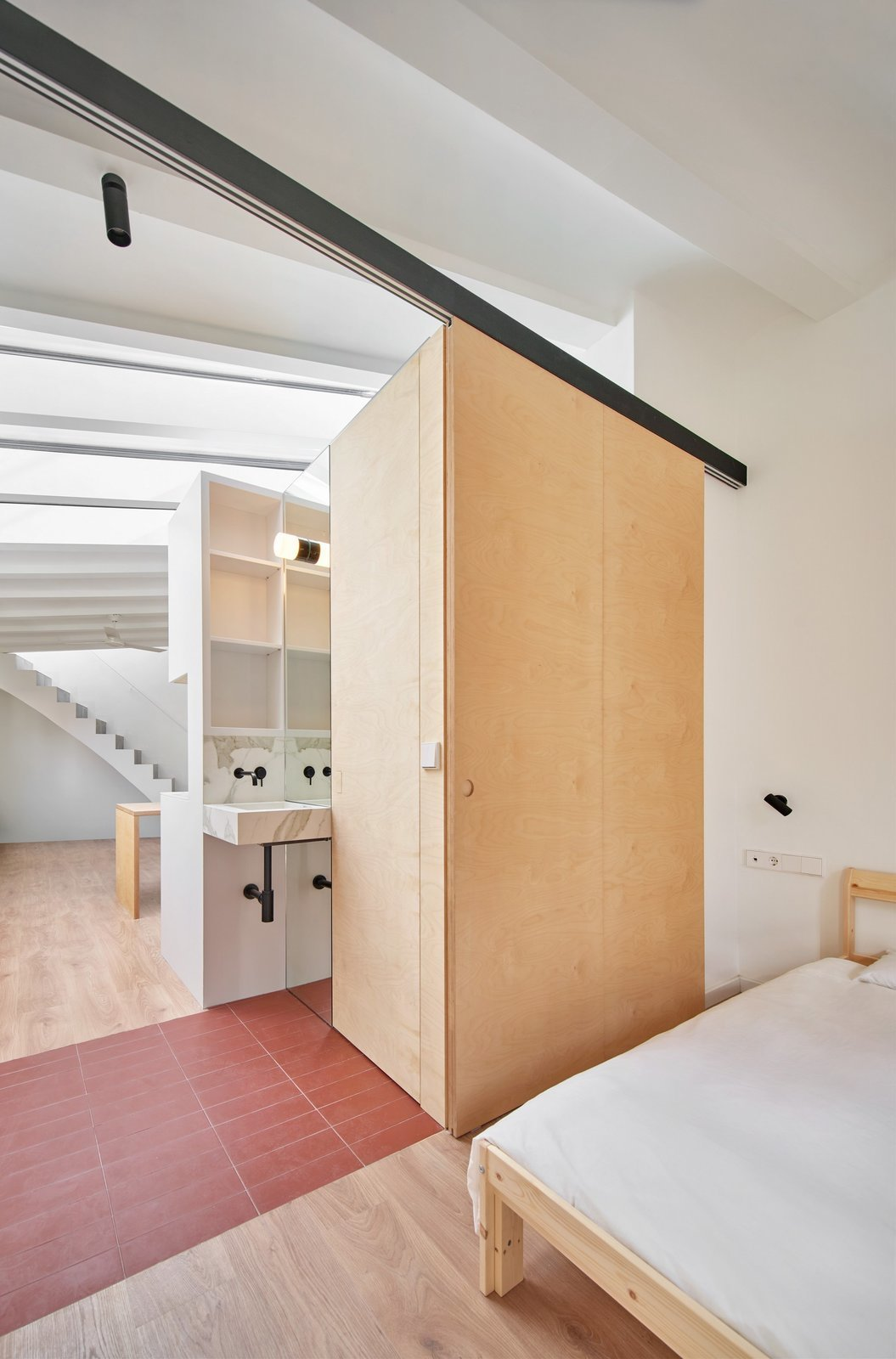 Bedroom, Track Lighting, Ceiling Lighting, Medium Hardwood Floor, and Bed  Photo 7 of 17 in Picture Windows and Sliding Doors Work Magic in This Cozy Barcelona Home