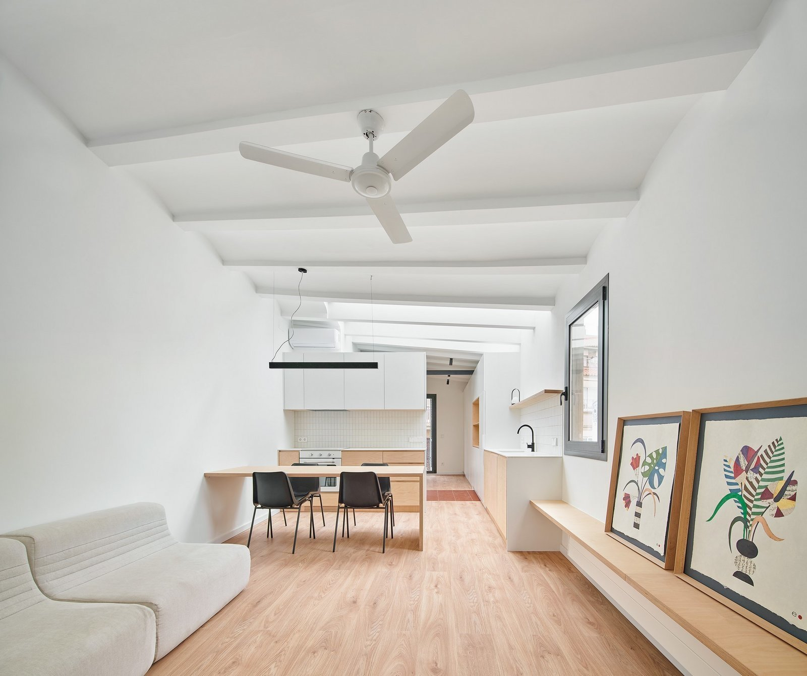 Living Room, Medium Hardwood Floor, Ceiling Lighting, Sofa, and Shelves  Photo 2 of 17 in Picture Windows and Sliding Doors Work Magic in This Cozy Barcelona Home