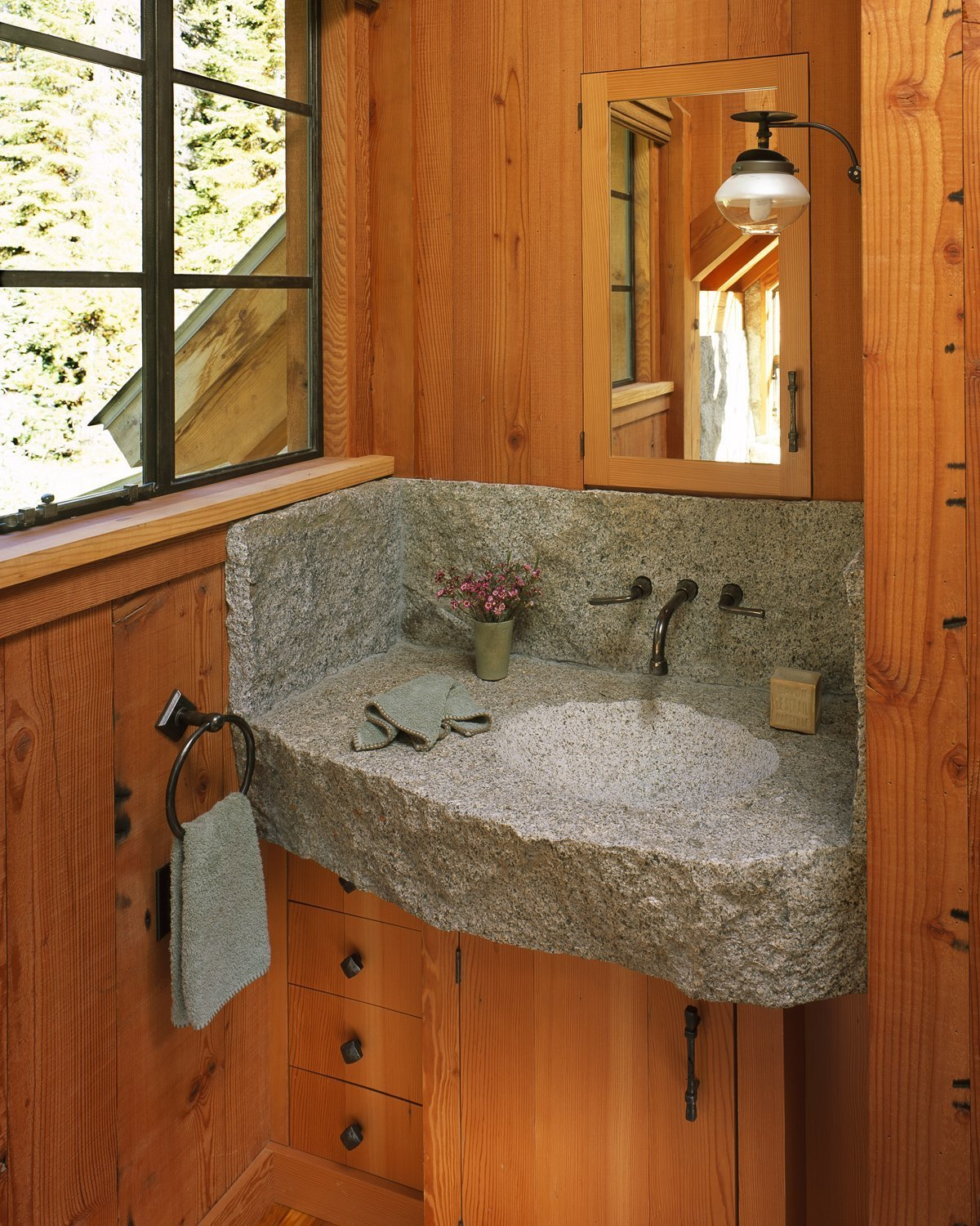 Bath Room, Concrete Counter, Medium Hardwood Floor, Wall Mount Sink, Wall Lighting, and Accent Lighting  Photo 7 of 11 in A Rustic Home Rivals the Rugged Beauty of Its Forest Setting