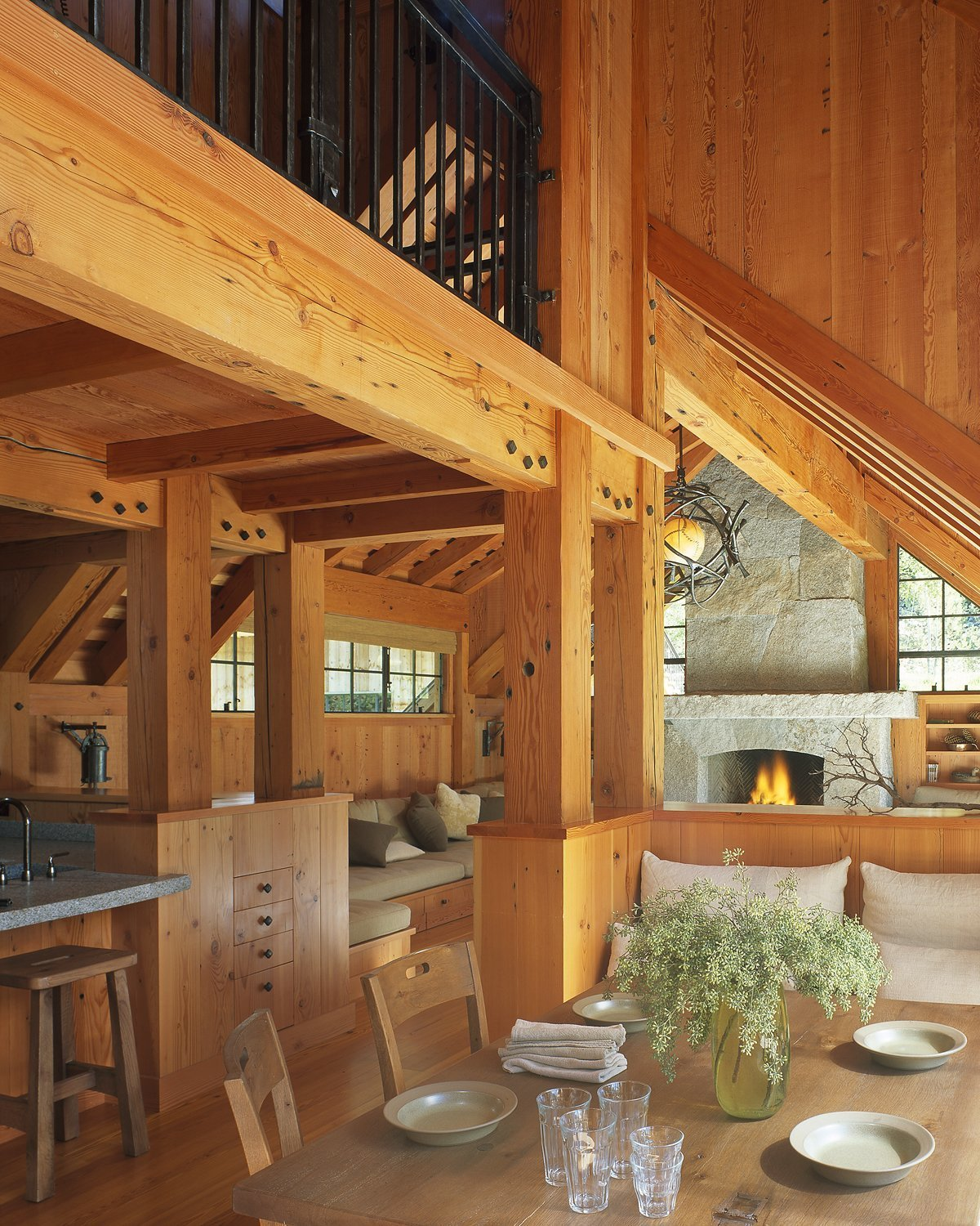 Dining Room, Medium Hardwood Floor, Table, Chair, Bench, and Standard Layout Fireplace  Photo 3 of 11 in A Rustic Home Rivals the Rugged Beauty of Its Forest Setting