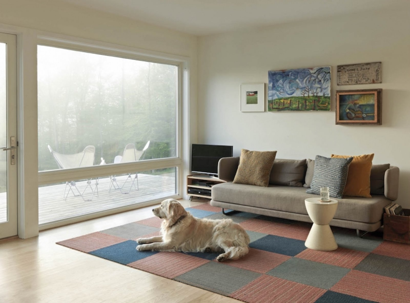 Living Room, Sofa, Console Tables, End Tables, Light Hardwood Floor, Stools, Rug Floor, and Media Cabinet  Photo 2 of 13 in A Little Black Cabin Keeps Things Simple for a Family of Four in Vermont