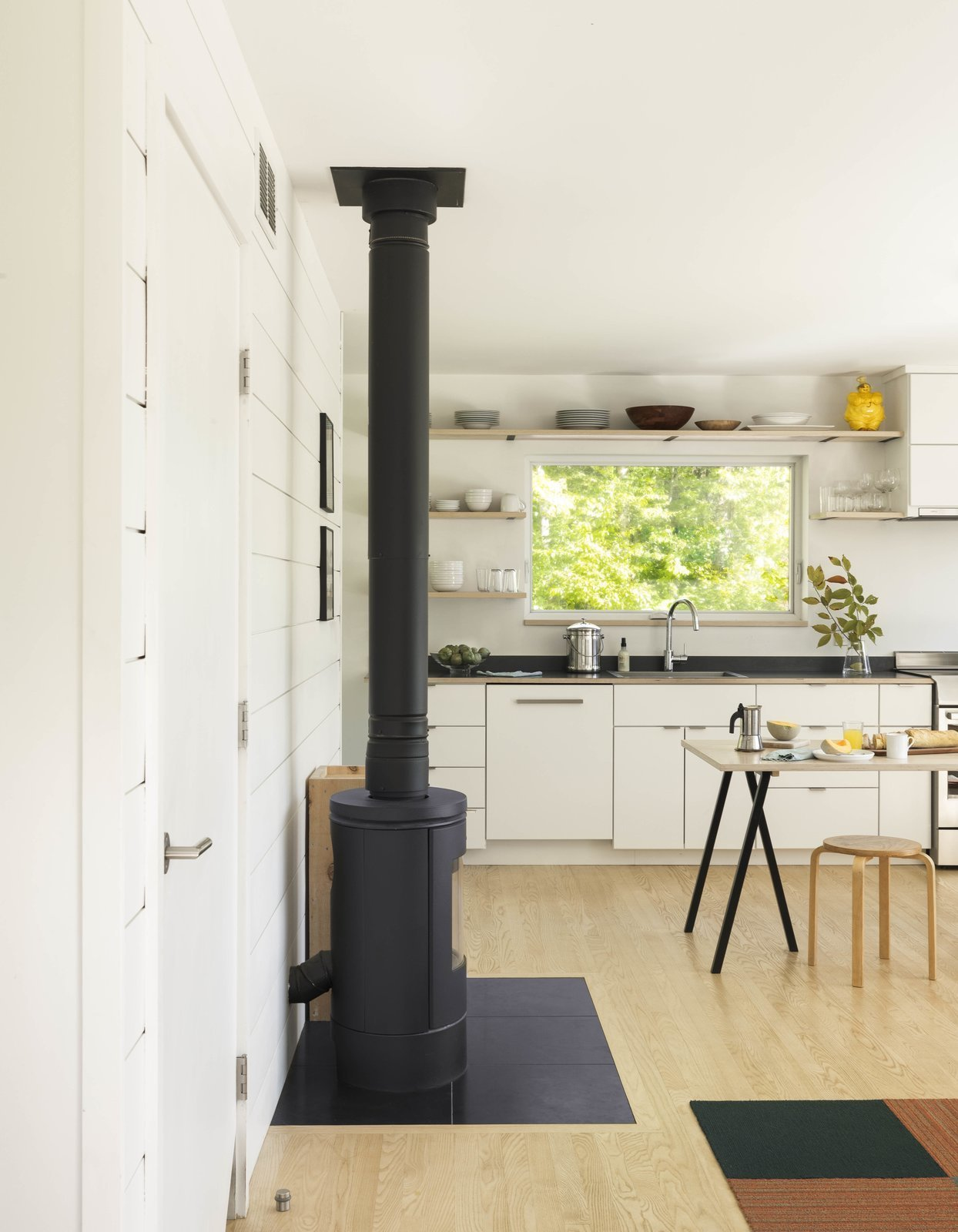 Kitchen, Laminate Counter, Drop In Sink, Wood Cabinet, White Cabinet, Light Hardwood Floor, Open Cabinet, and Dishwasher  Photo 10 of 13 in A Little Black Cabin Keeps Things Simple for a Family of Four in Vermont