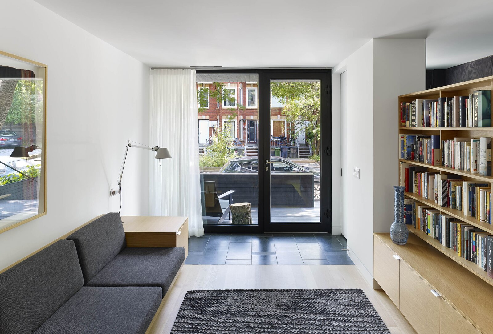 Living Room, Rug Floor, Light Hardwood Floor, Wall Lighting, Shelves, Sofa, and Storage  Photo 6 of 16 in An Architect Couple Turn an Urban Eyesore Into a Home That's Both Peaceful and Playful from Bellwoods Lodge