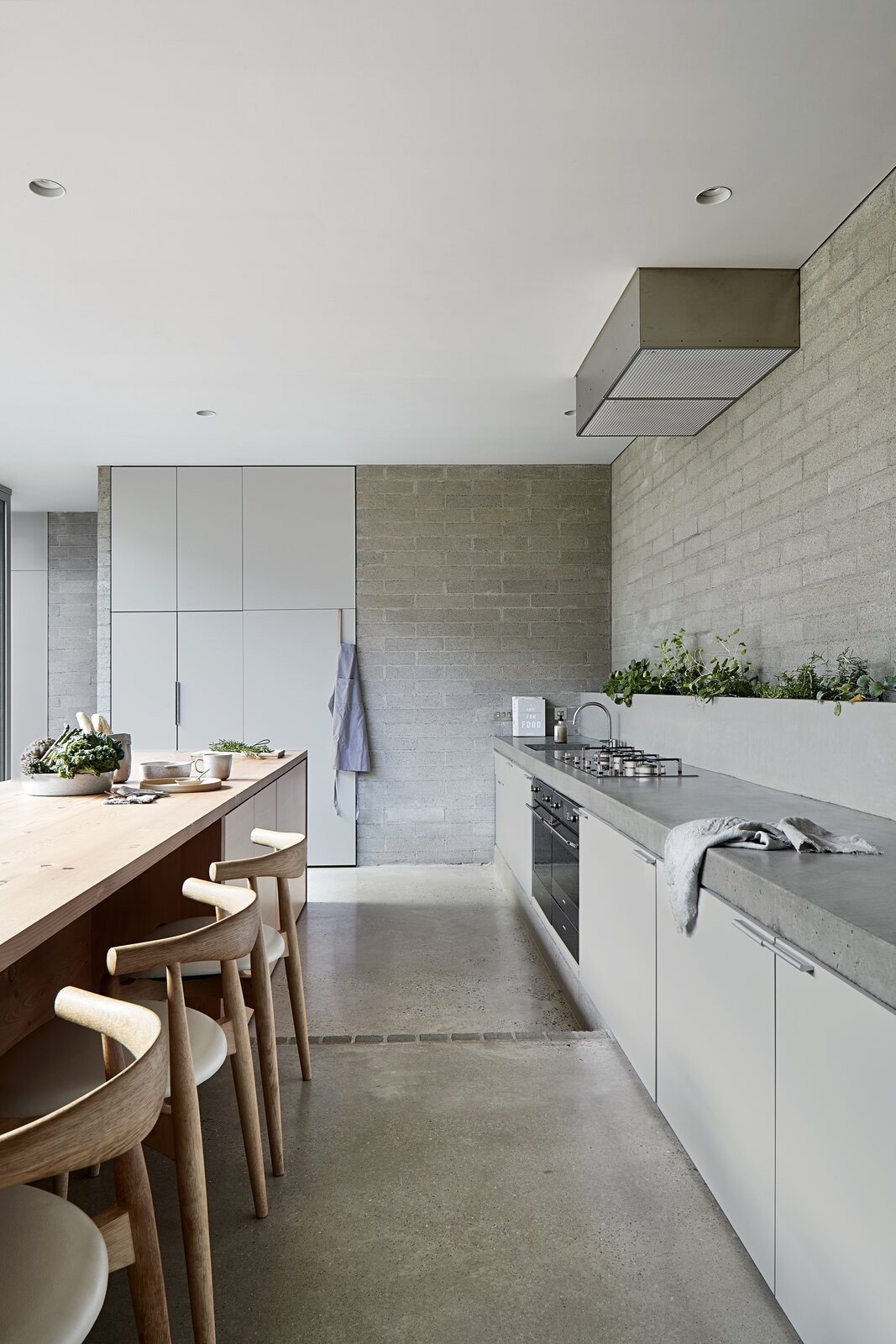 Kitchen, Concrete Counter, Concrete Floor, Brick Backsplashe, Range, Recessed Lighting, Cooktops, and Range Hood  Photo 2 of 20 in A Concrete House Is Softened by an Airy Internal Courtyard, Complete With an Olive Grove from Ruxton Rise Residence