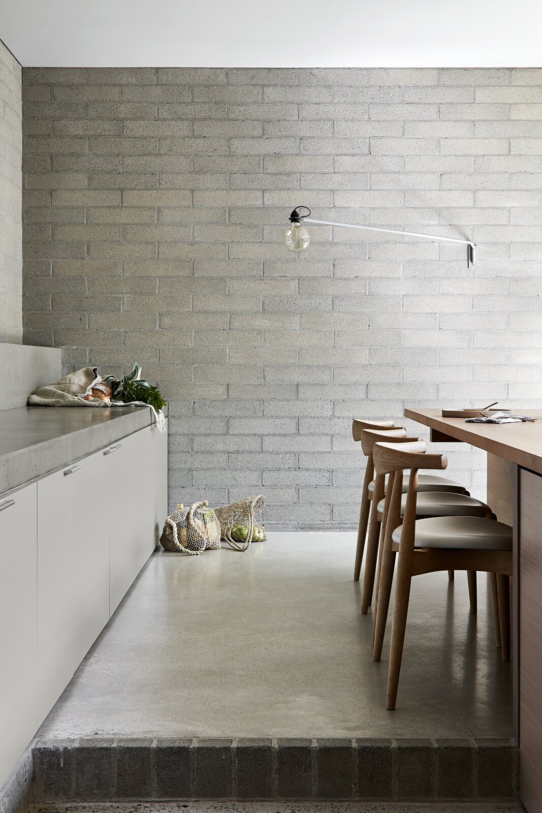 Kitchen, Concrete Floor, Brick Backsplashe, Wall Lighting, and Concrete Counter  Photo 8 of 20 in A Concrete House Is Softened by an Airy Internal Courtyard, Complete With an Olive Grove from Ruxton Rise Residence