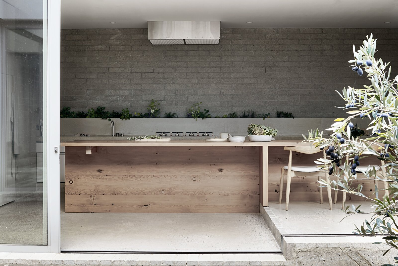Kitchen, Concrete, Recessed, Concrete, Cooktops, Ceiling, Brick, Range, and Range Hood  Kitchen Concrete Cooktops Photos from A Concrete House Is Softened by an Airy Internal Courtyard, Complete With an Olive Grove
