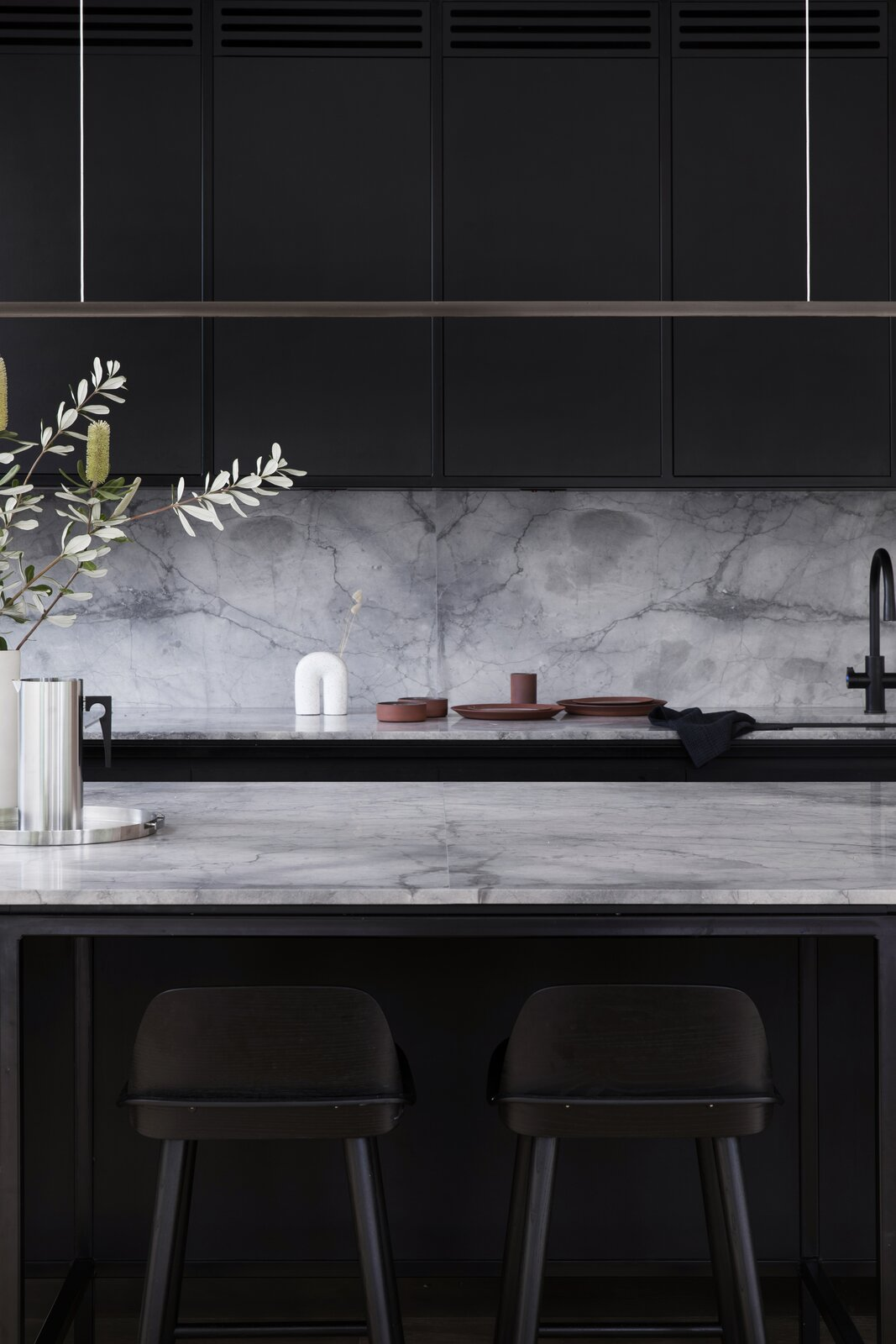 Cnr Virginia by Studio Prineas black kitchen with gray marble countertops and backsplash