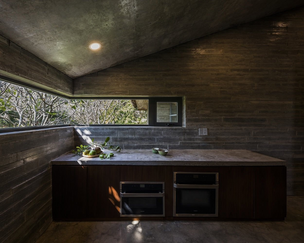 Kitchen, Concrete Counter, Wall Oven, Concrete Floor, Ceiling Lighting, and Microwave  Photo 8 of 16 in A Koi-Filled Moat Surrounds This Vietnamese House from Am house