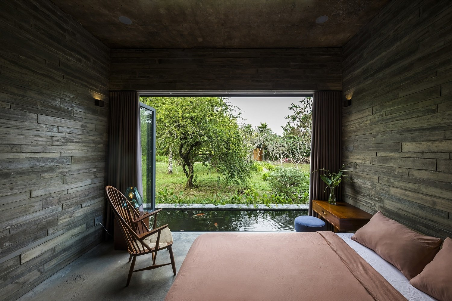 Bedroom, Bed, Chair, Concrete Floor, Ceiling Lighting, and Pendant Lighting  Photo 11 of 16 in A Koi-Filled Moat Surrounds This Vietnamese House from Am house