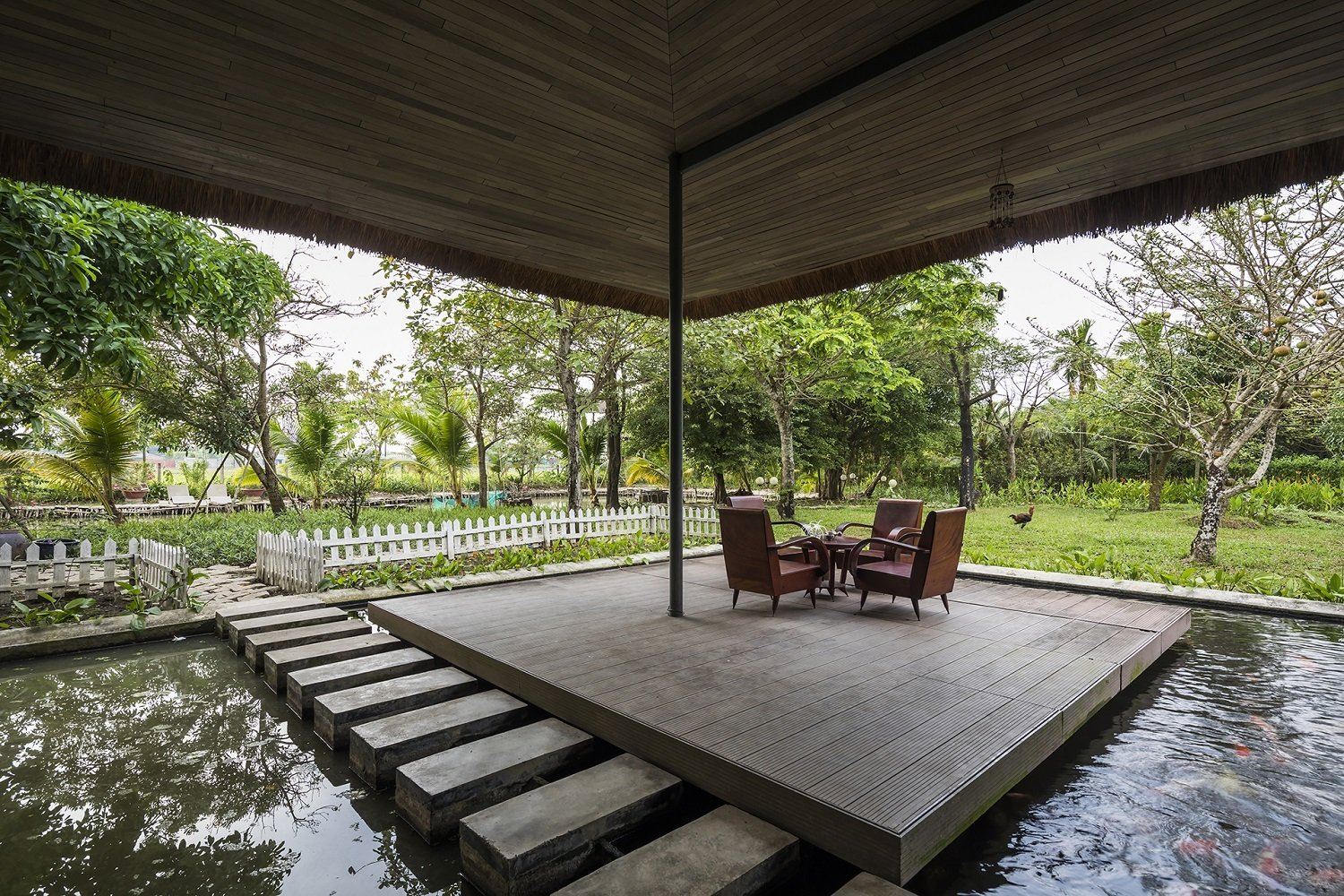 Outdoor, Garden, Gardens, Decking Patio, Porch, Deck, Small Pools, Tubs, Shower, and Small Patio, Porch, Deck  Photo 9 of 16 in A Koi-Filled Moat Surrounds This Vietnamese House from Am house
