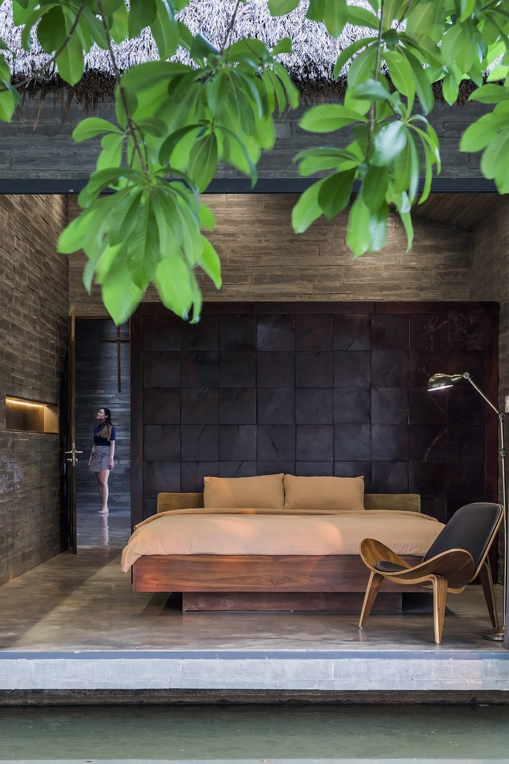 Bedroom, Ceiling Lighting, Bed, Concrete Floor, and Chair  Photo 6 of 16 in A Koi-Filled Moat Surrounds This Vietnamese House from Am house
