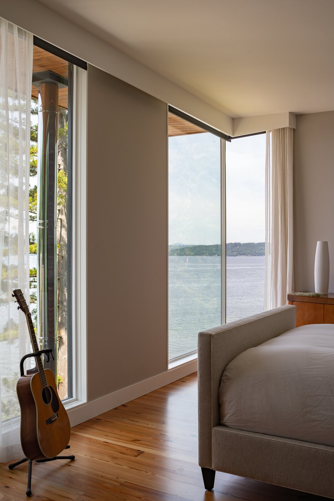Bedroom, Medium Hardwood Floor, and Bed  Photo 10 of 13 in A Waterfront Home in Washington Grows Two Hovering Wings